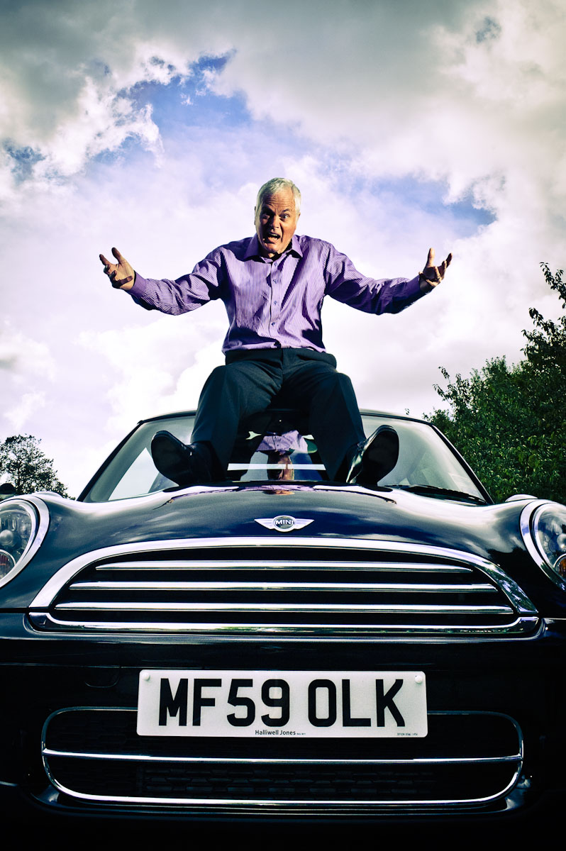 Duncan McKenzie sat on roof of Mini car