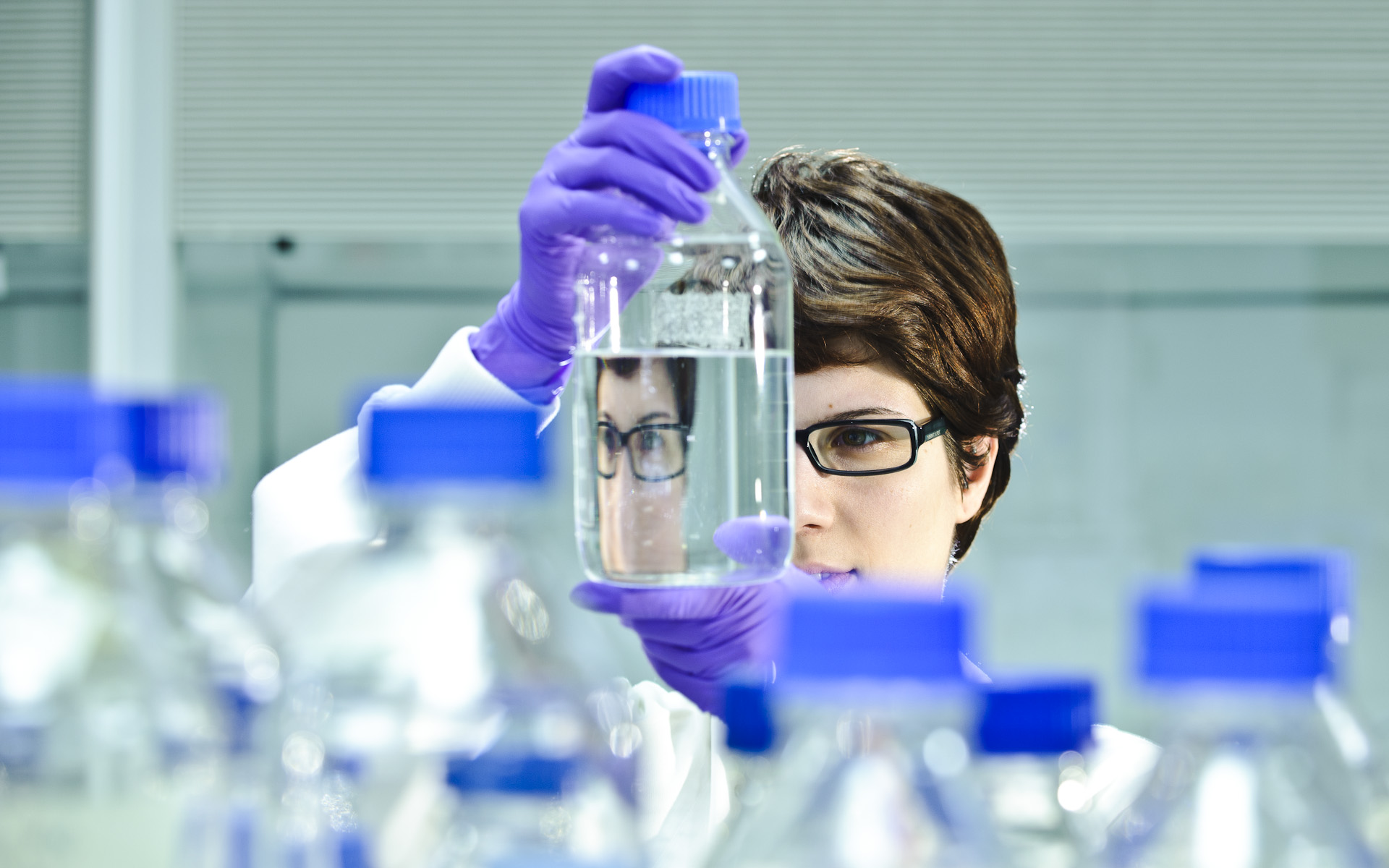 Scientist looking at clear liquid in flask