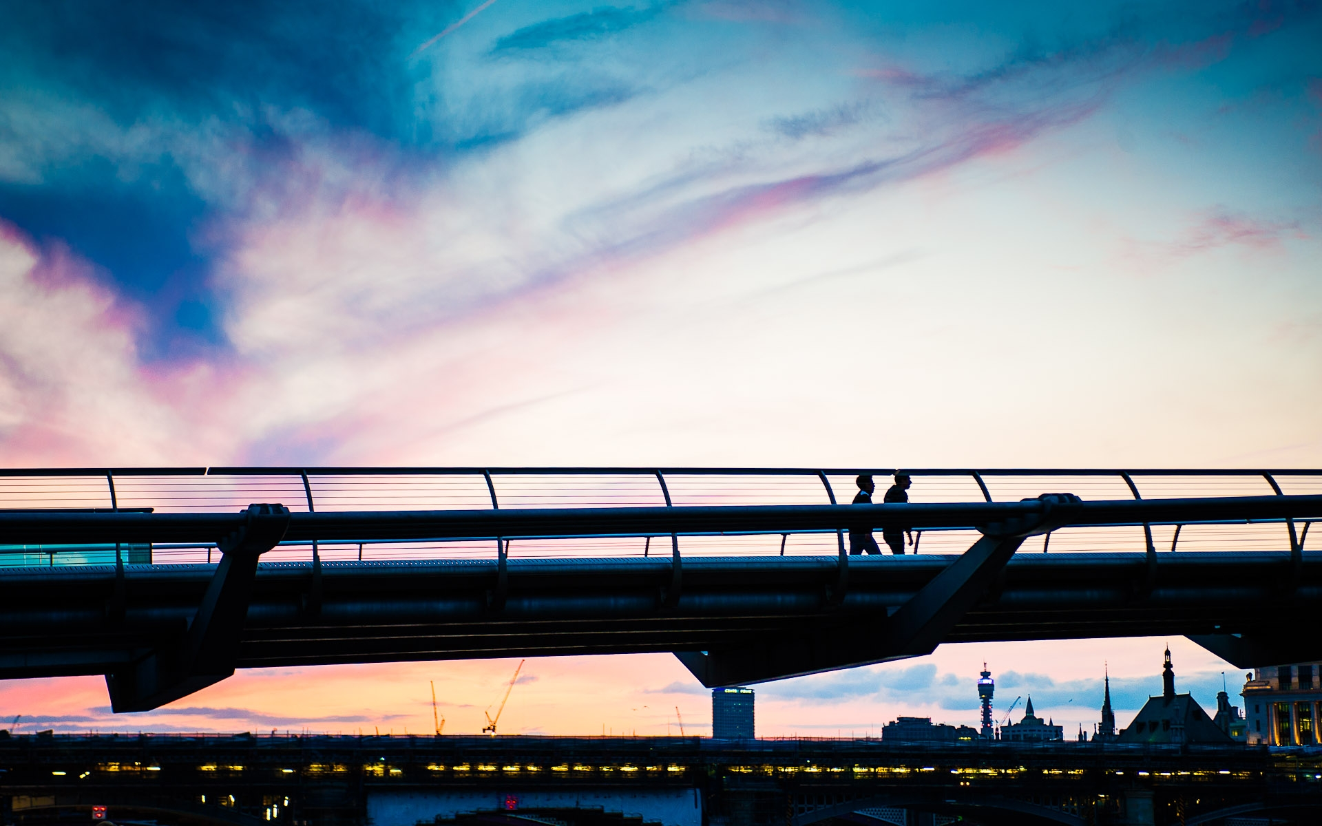 people in silhouette waling across london millenium bridge at disk against colourful sky