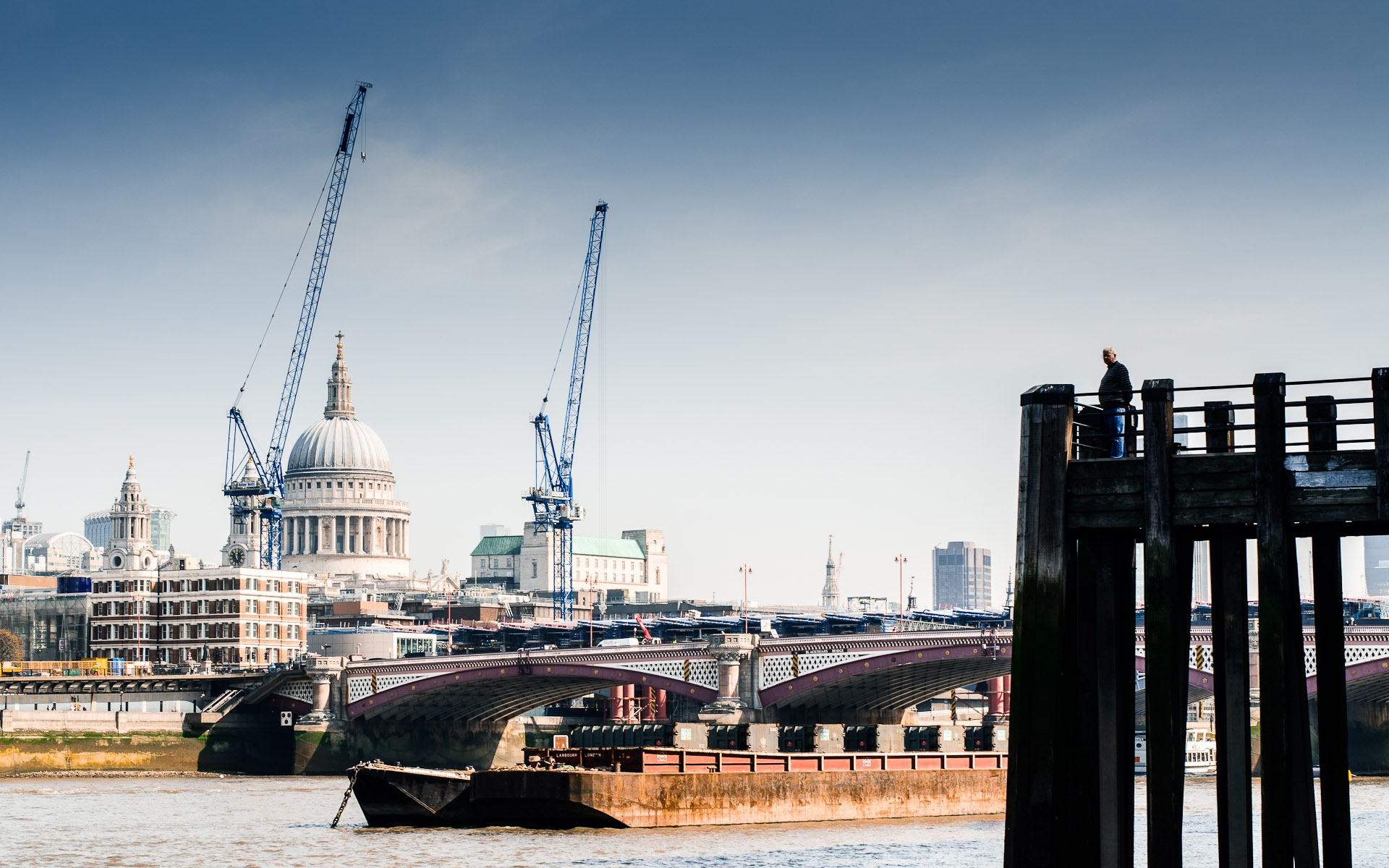 man looking out over river thames construction cranes by st pauls