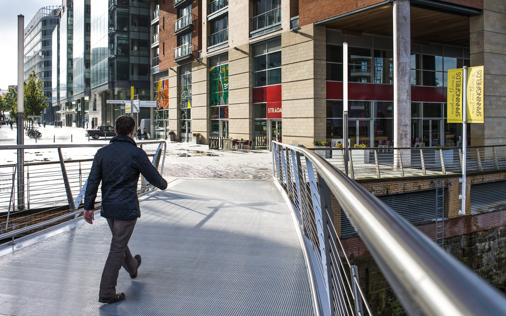 Man walking across footbridge to Manchester Spinningfields