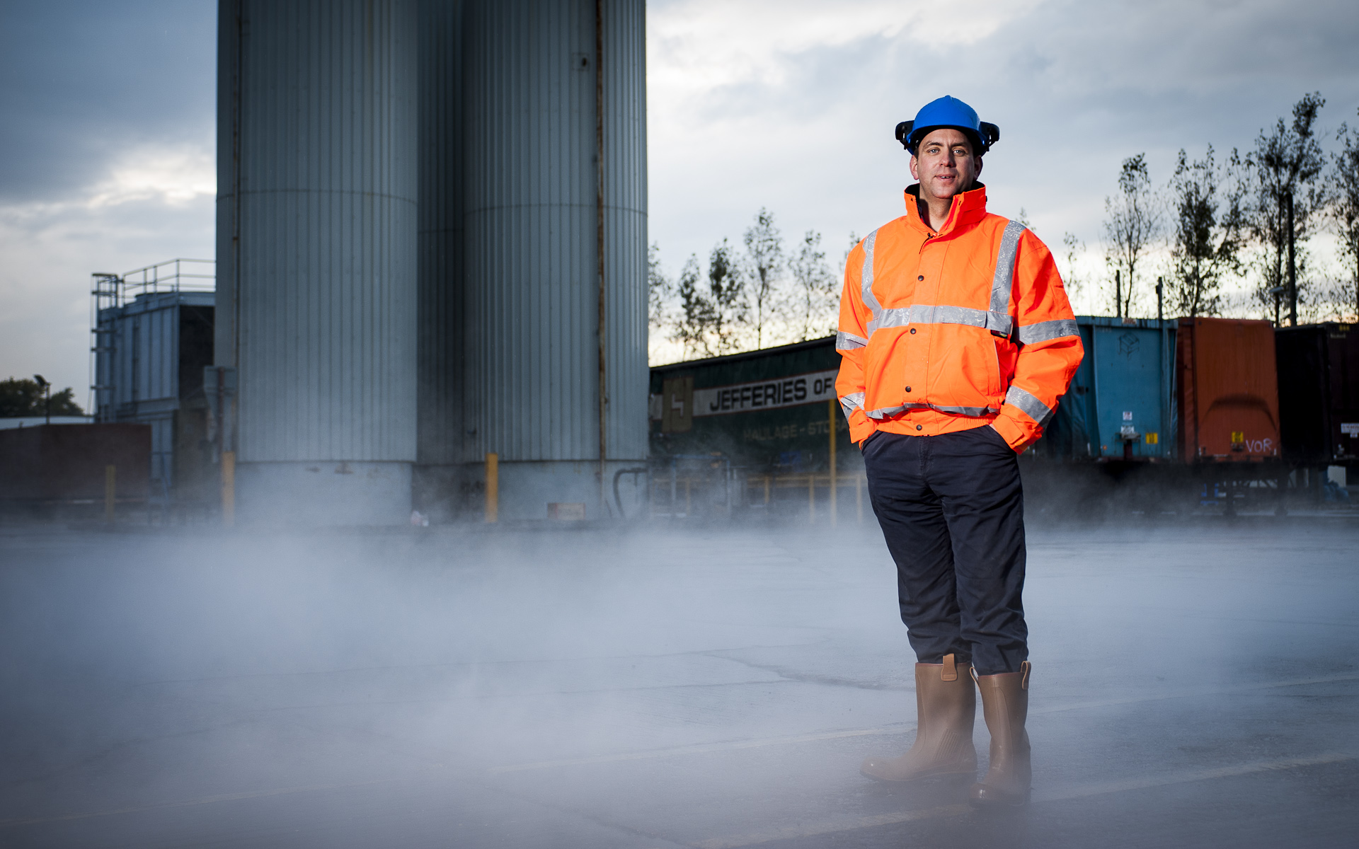 man in hard hat high vis ppe standing in smoky industrial yard