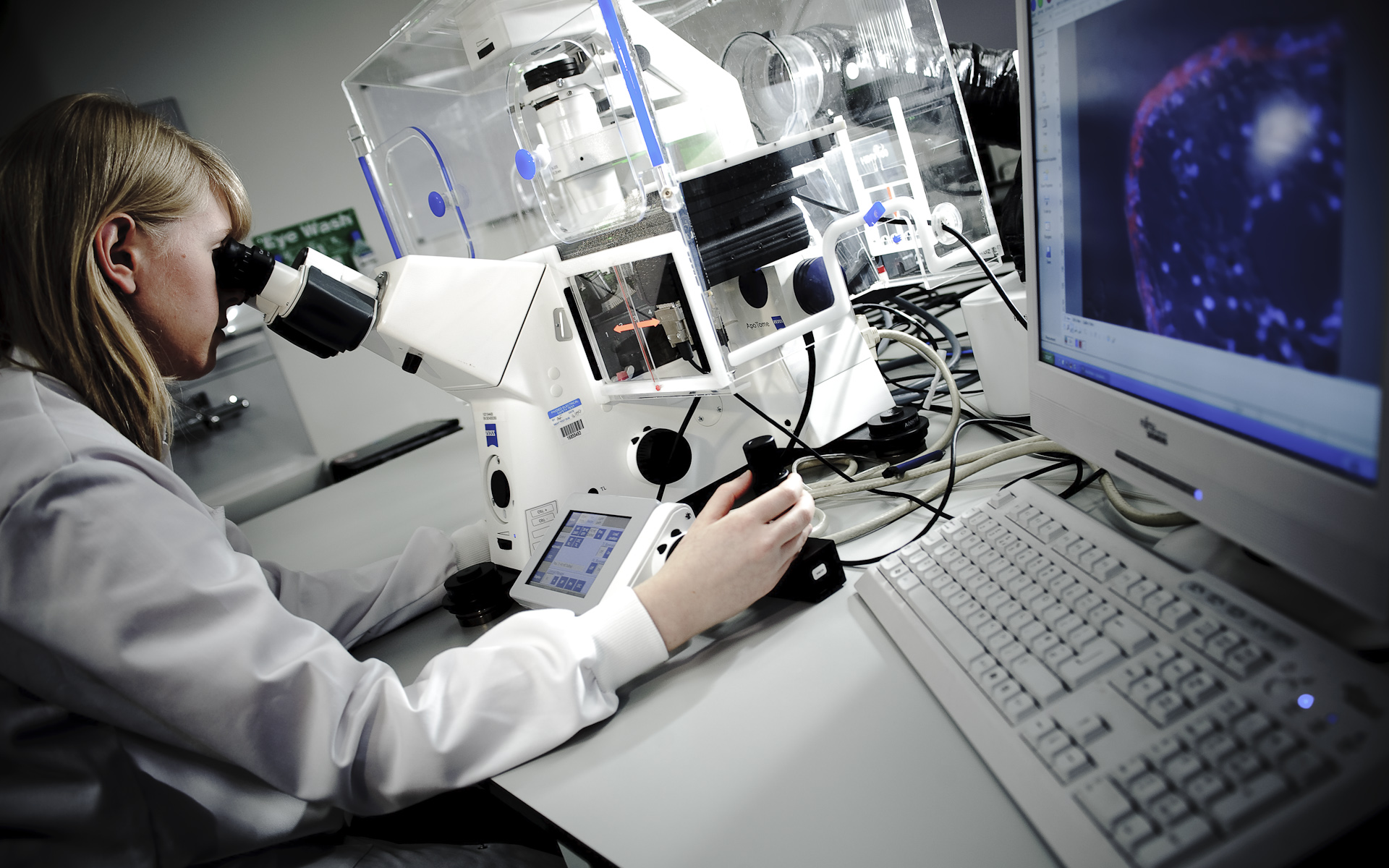 female science student at powerful microscope in science lab