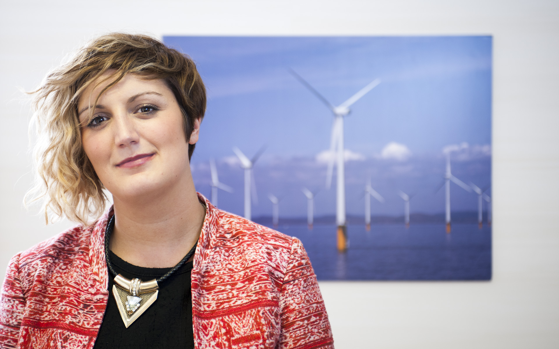 portrait of woman in front of picture of wind turbines