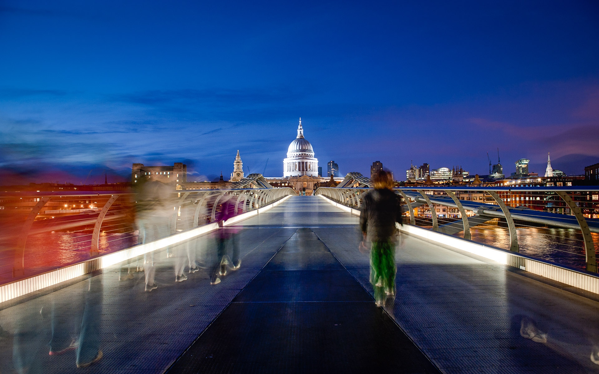 people walking across millennium bridge towards st pauls at night
