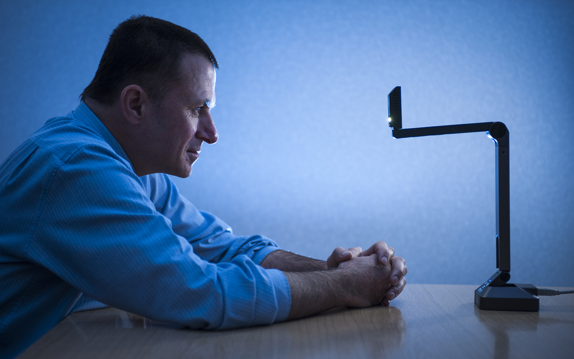 editorial photography of man looking at light across desk