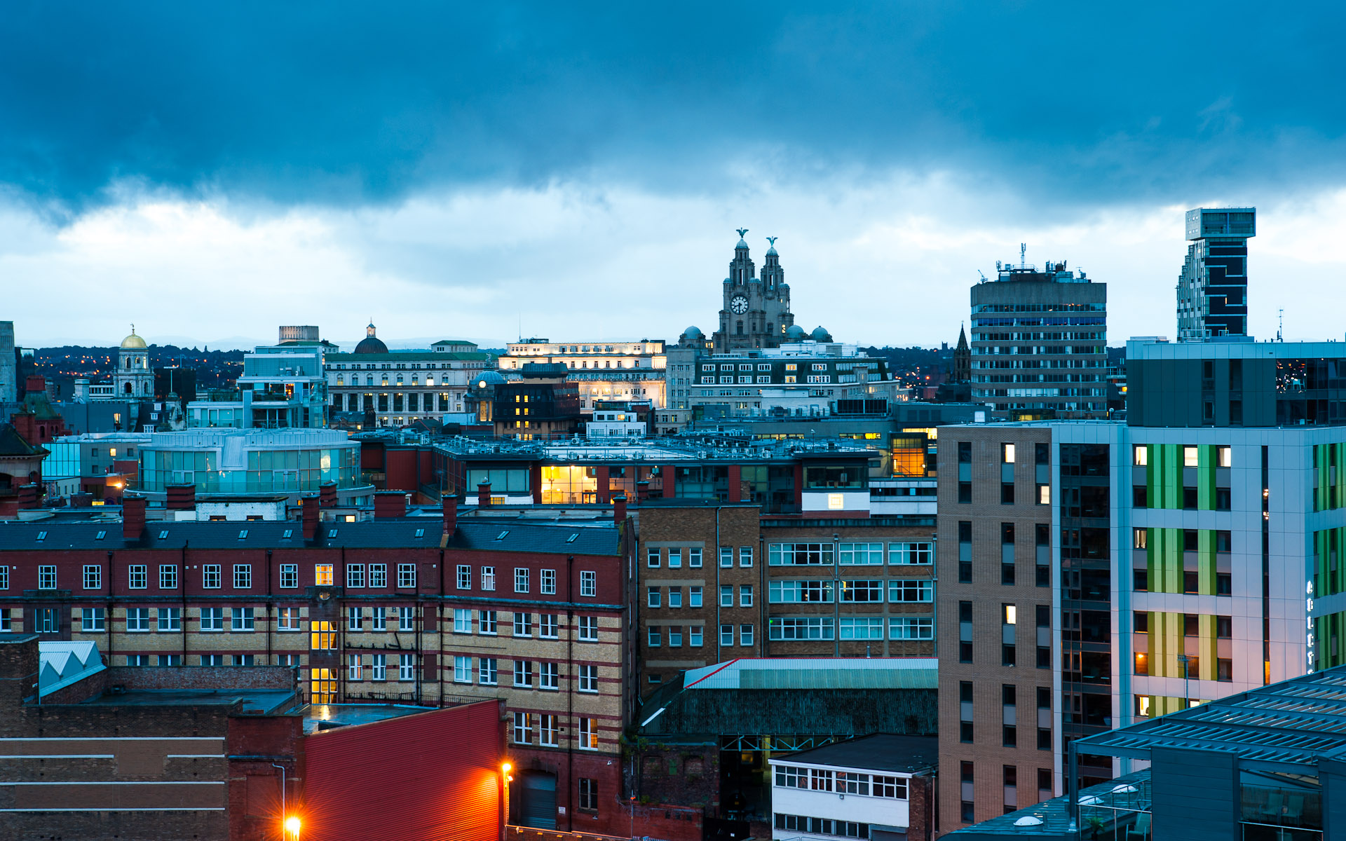 Liver building Liverpool across city rooftops at dusk night