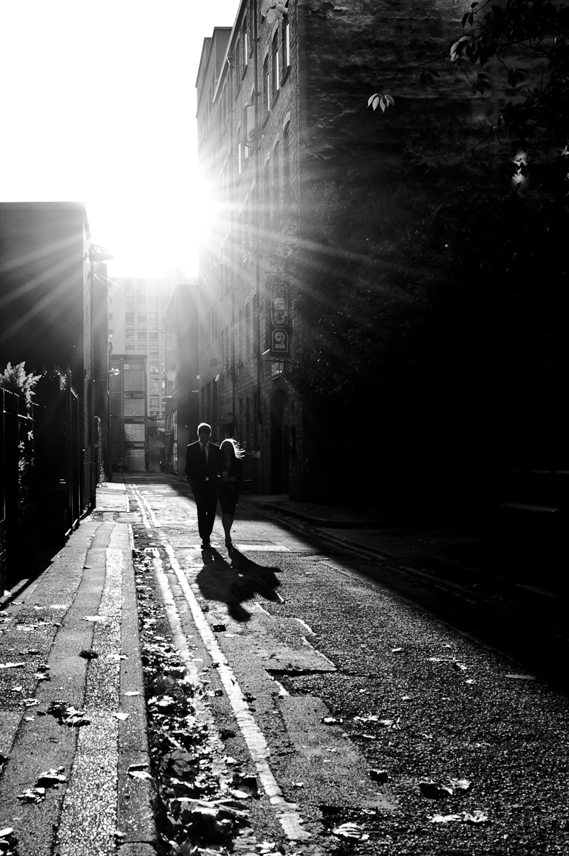 Couple walking down Manchester side street backlit sun black and white