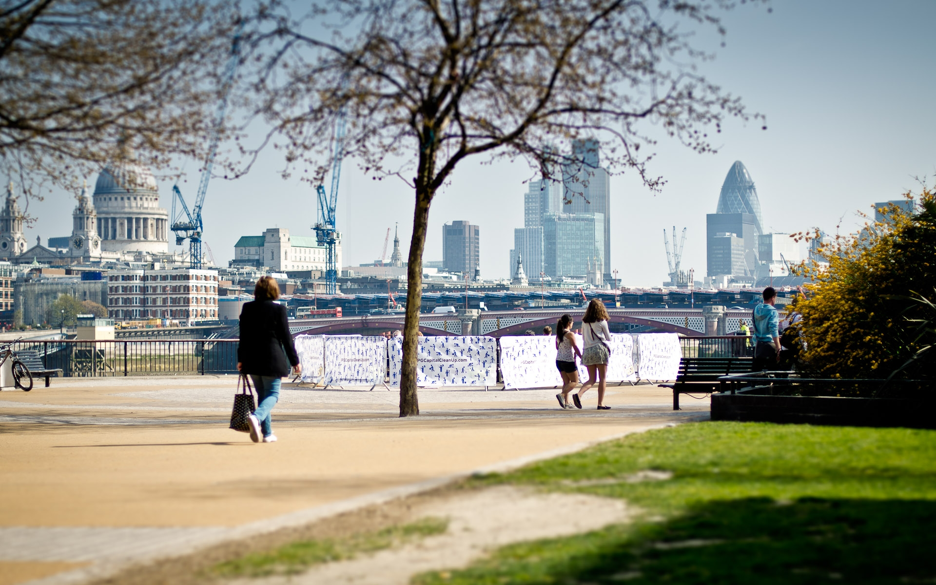people walking along south bank by river thames london with city skyline