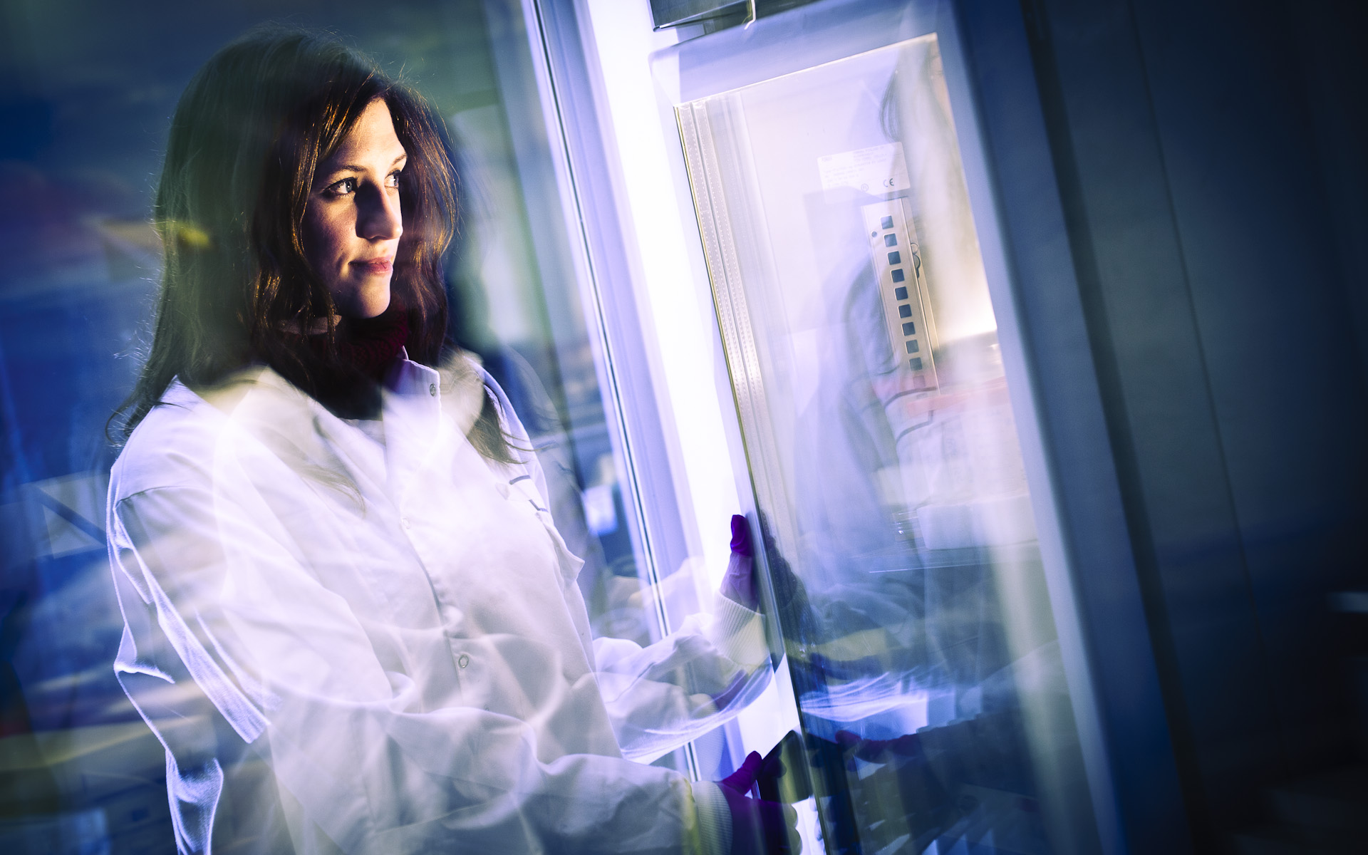 young female science student in white lab coat at fridge