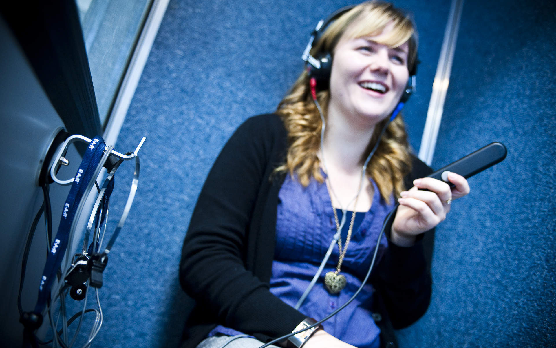 female audiology student in sound booth wearing headphones
