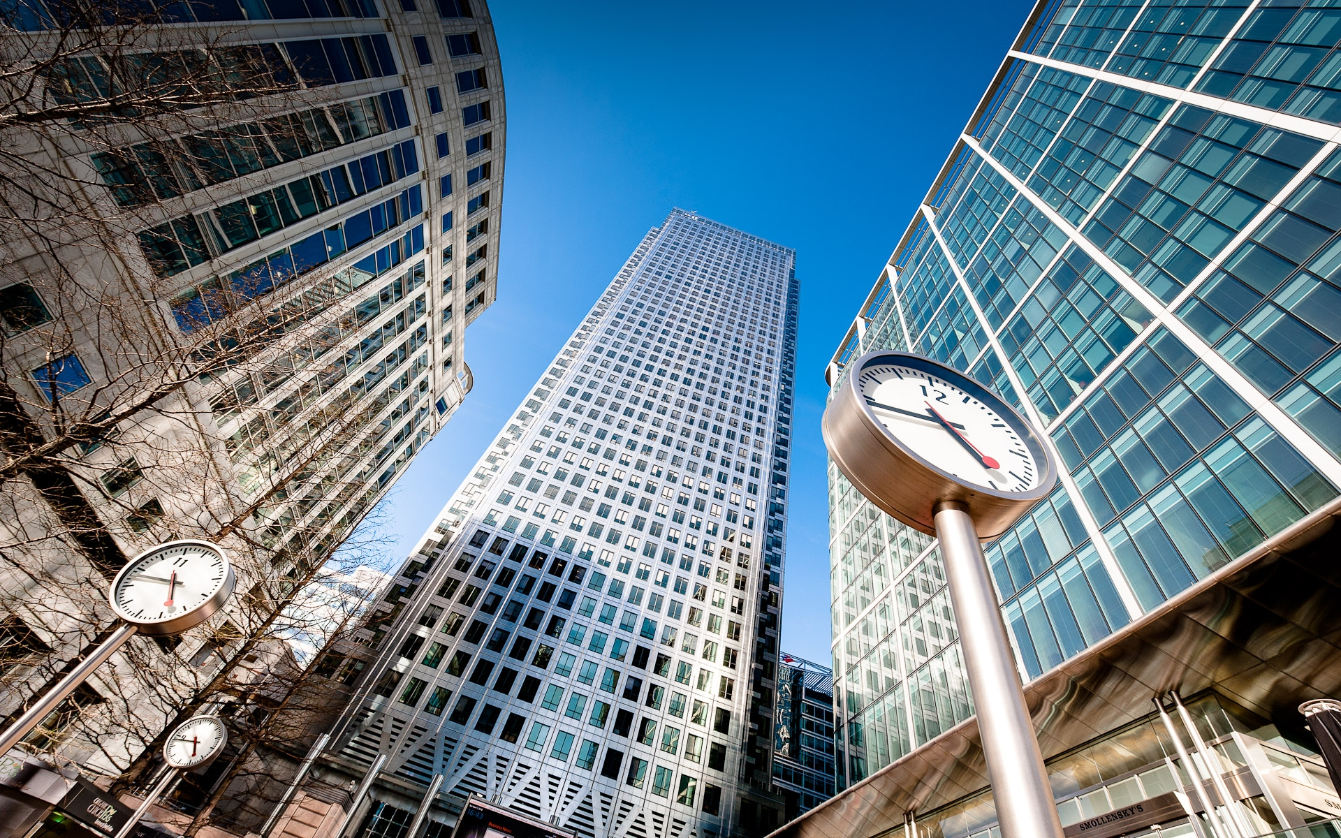 up shot of canary wharf one canada square with clocks in foreground