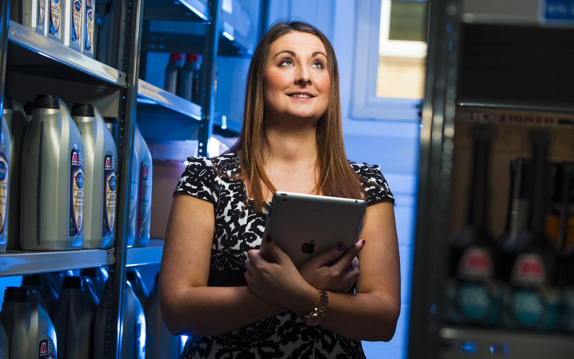 woman holding ipad amongst store room of engine oil