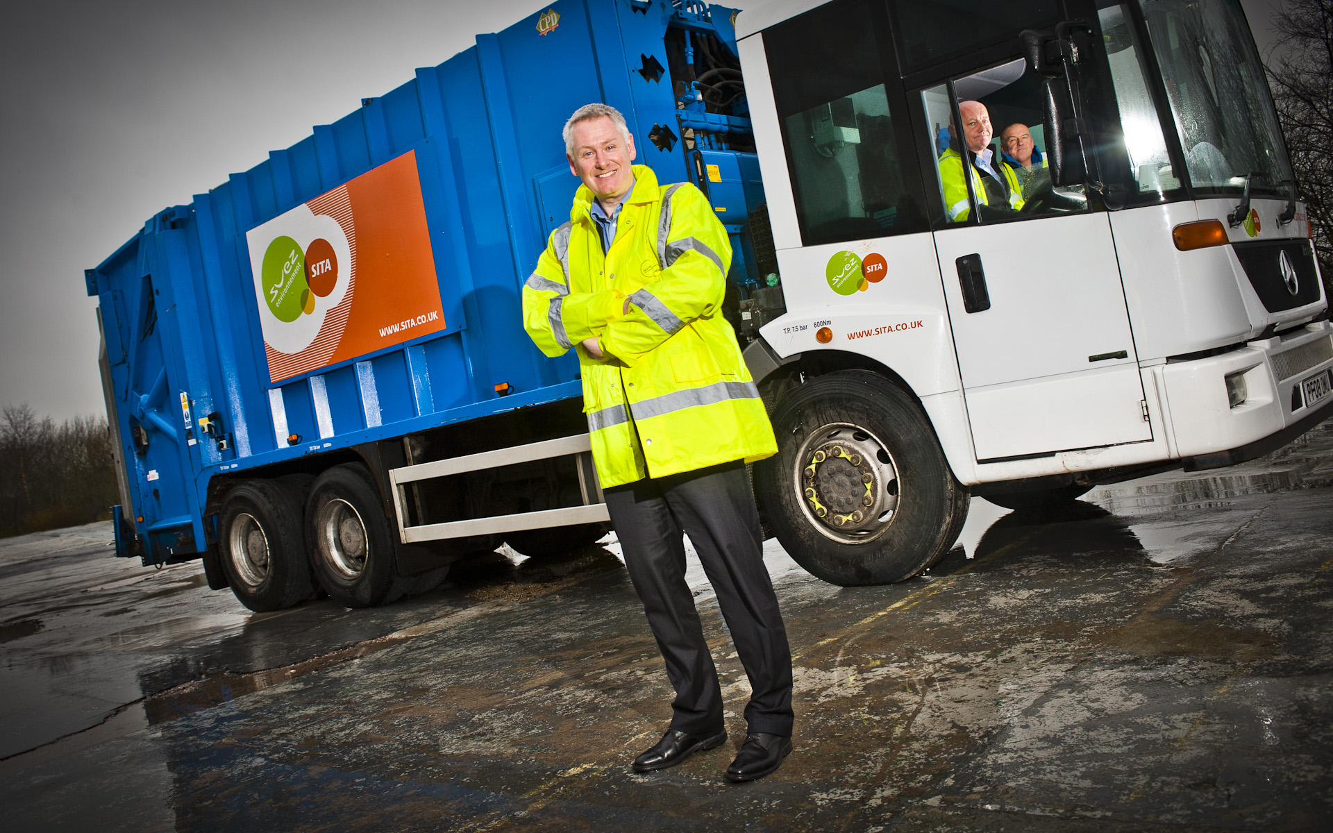 Man by SITA SUEZ refuse collection bin lorry