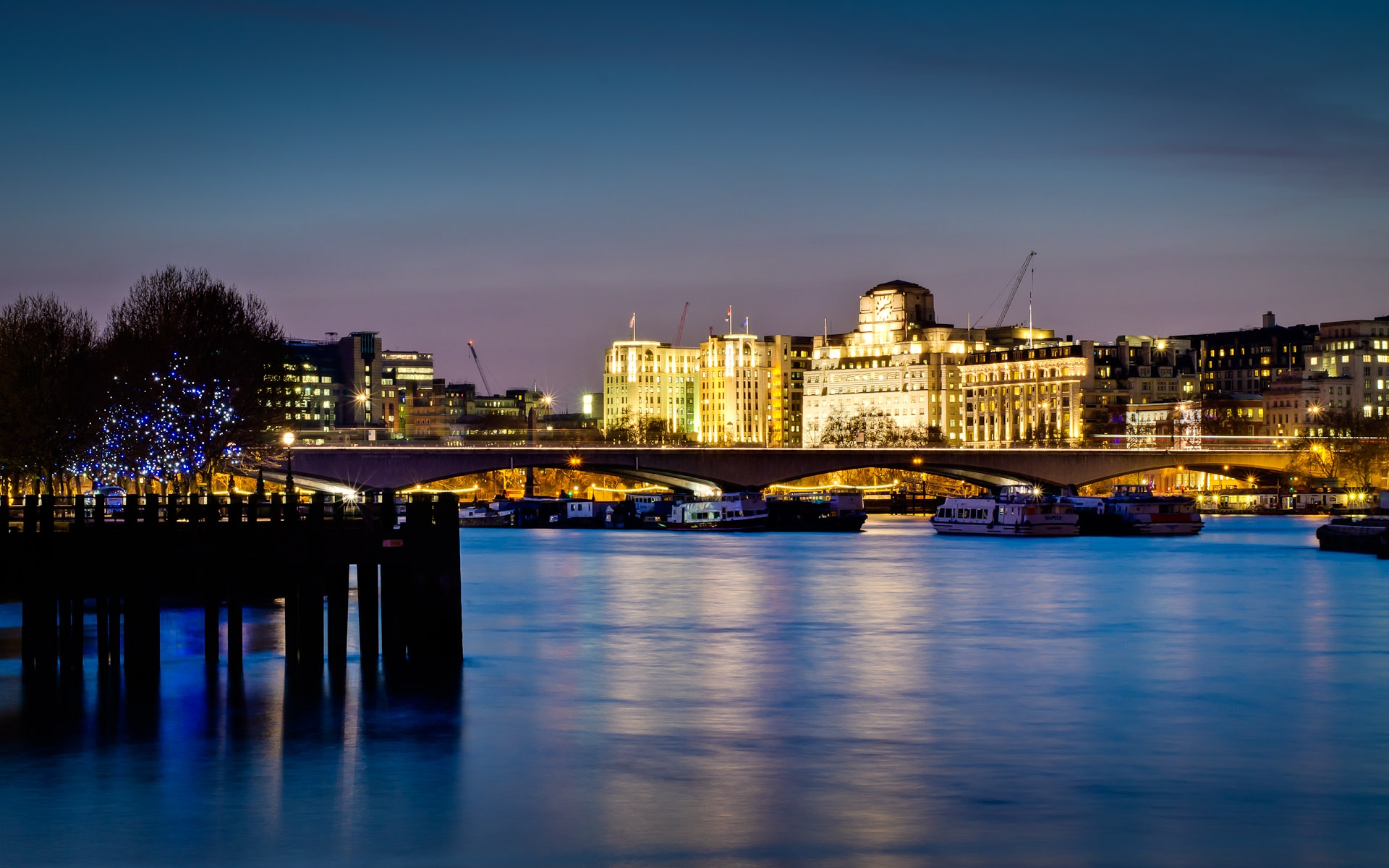 view of MI6 building across river thames london at night