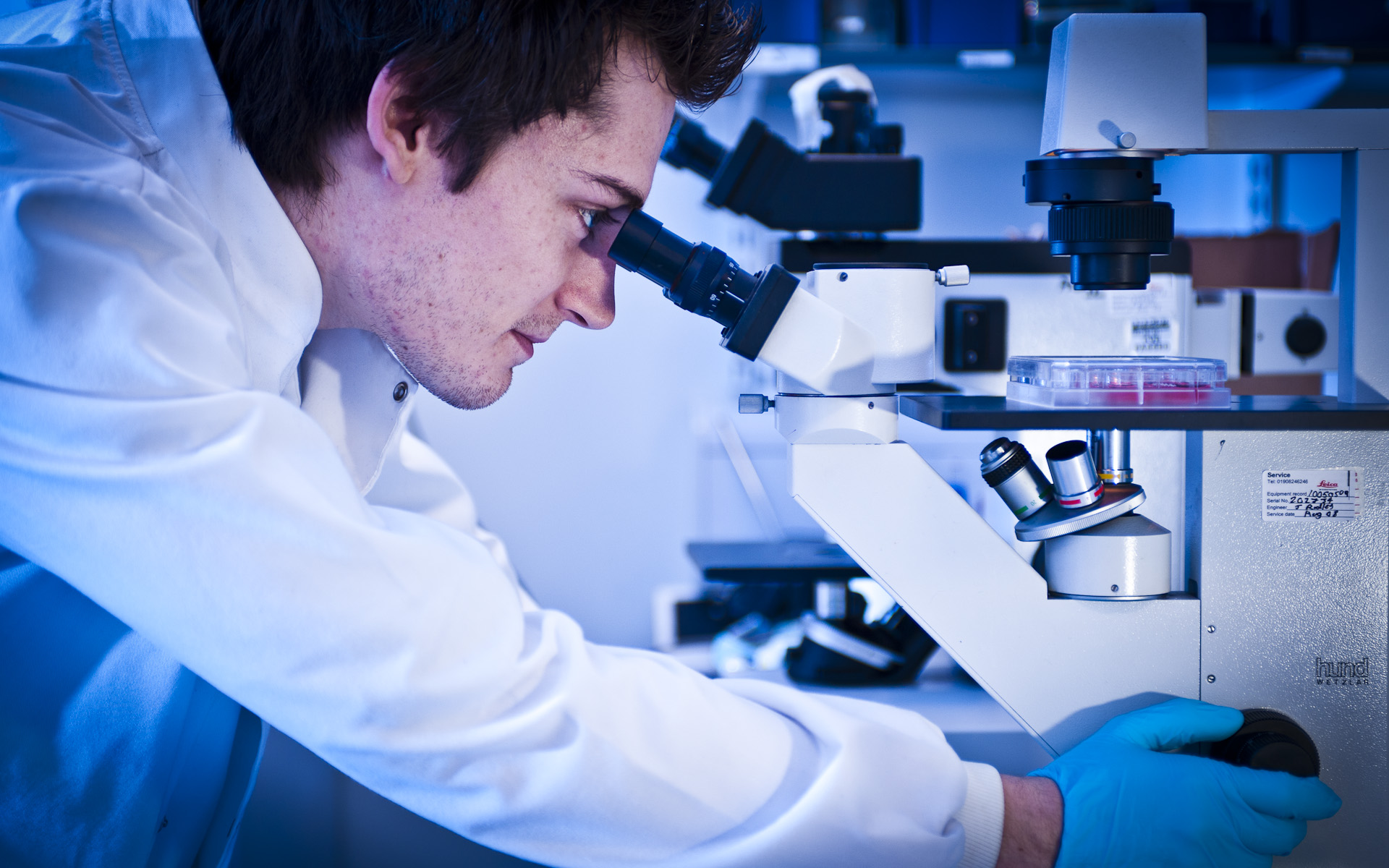 young male science student looking down microscope