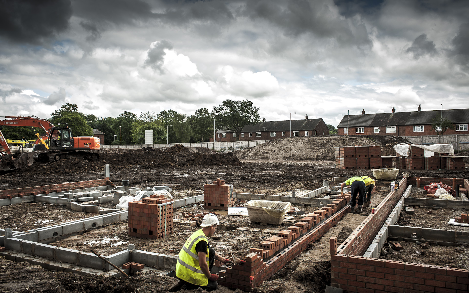 builders laying foundations on residential building site